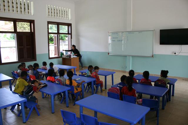 새로 마련된 어린이용 책상과 의자와 수업받는 미취학아동들(시청각을 위한 TV포함).jpg