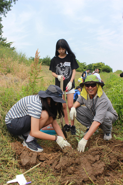 법일 스님과 청소년들이 함께 버드나무를 심고 있다.jpg