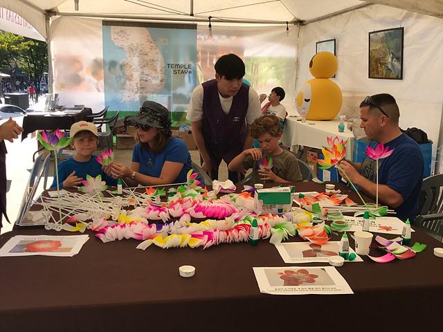템플스테이 홍보부스에서 연꽃 만들기를 하는 외국인 참가자들.jpg