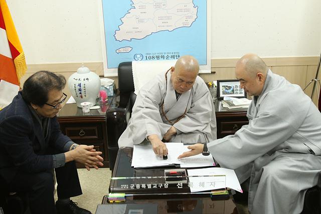 선묵혜자 스님이 계약서에 도장을 찍고 있는 모습. 왼쪽은 금성 이석범 대표, 오른쪽은 사무총장 성진 스님이다.jpg