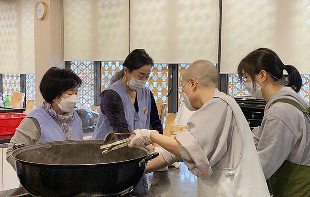 200310_한국불교문화사업단이 운영하는 한국사찰음식문화체험관에서 스님과 자원봉사자들이 도시락을 만들고 있다.jpg
